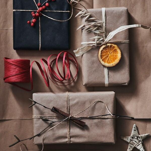 Paket i naturfärger dekorerade med snören, torkade apelsinklyftor och stjärnor sedda uppifrån.