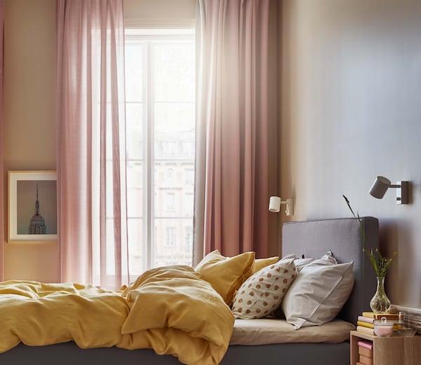 Paksut ja ohuet verhot lämpimän värisessä makuuhuoneessa.