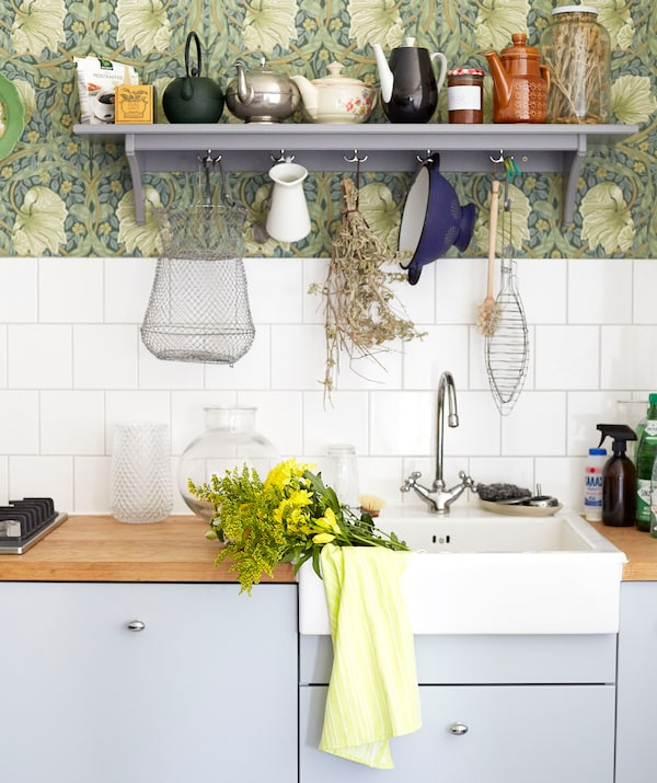 Pale grey kitchen cupboards, wooden worktops and a white sink, with white tiles and a grey shelf above.