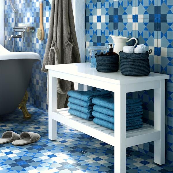 Panca bianca con asciugamani piegati sul ripiano in basso e accessori sul piano superiore, pareti e pavimento di piastrelle azzurre - IKEA
