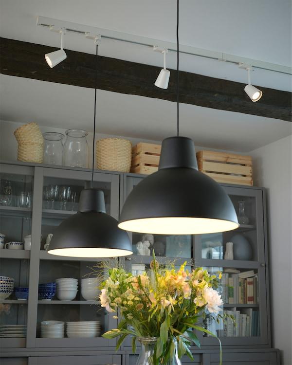 Pandangan siling yang menunjukkan dua lampu pendan berwarna hitam dan tiga lampu sorot LED berwarna putih.