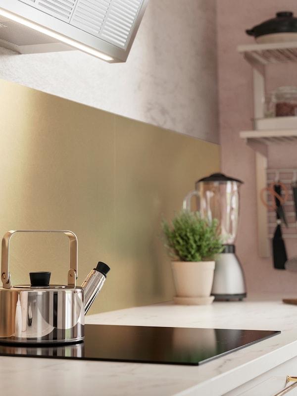 Panel dinding LYSEKIL berwarna loyang di belakang permukaan atas kerja dapur dengan kesan marmar dan teko teh keluli tahan karat pada hob.