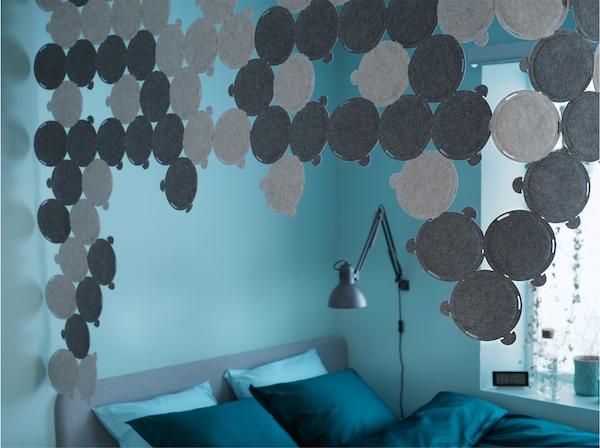 Paneles de insonorización grises montados en el techo que rodean una cama en un dormitorio azul y verde.