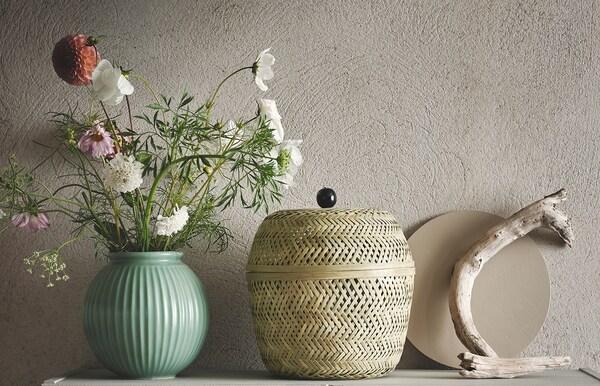 Panier en bambou TJILLEVIPS avec couvercle à côté d'un vase vert rempli de fleurs.