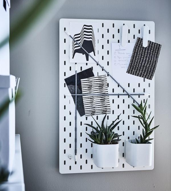 Panneau perforé SKÅDIS installé au mur, plantes et papiers y trouvent leur place.