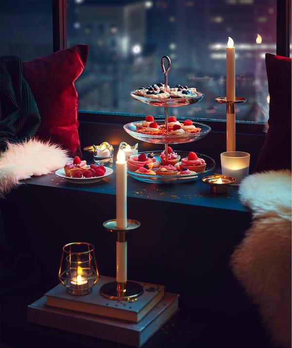 Panoráma mesta za oknom s dobrotami na servírovacích stojanoch na parapete a útulné sedenie so sviečkami LED.