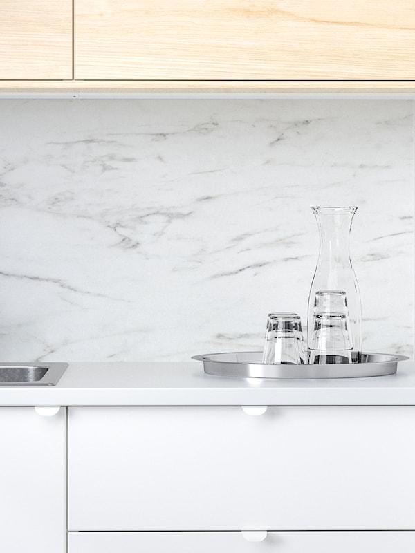 Panou de perete SIBBARP alb cu efect de marmură într-o bucătărie cu fronturi alb și fag, o tavă cu pahare și o carafă.