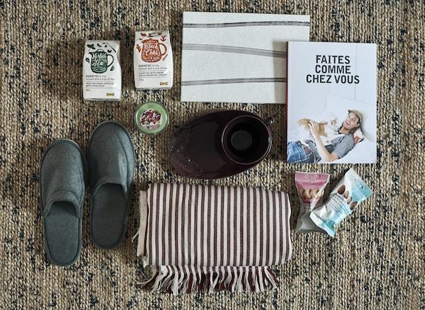 Pantofole, libri, articoli per la casa e snack disposti su un tappeto - IKEA