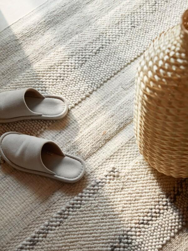Pantoufles de couleur crème et vase en bambou tressé posés sur un tapis BRÖNDEN tisséà la main.