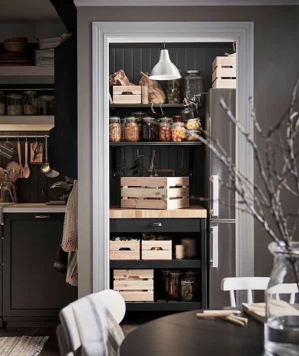 Pantry-like kitchen section; kitchen island with wooden crates snugly placed in corner underneath shelves with pickle jars.