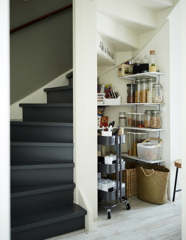 Pantry shelves and a trolley in an alcove under the stairs.