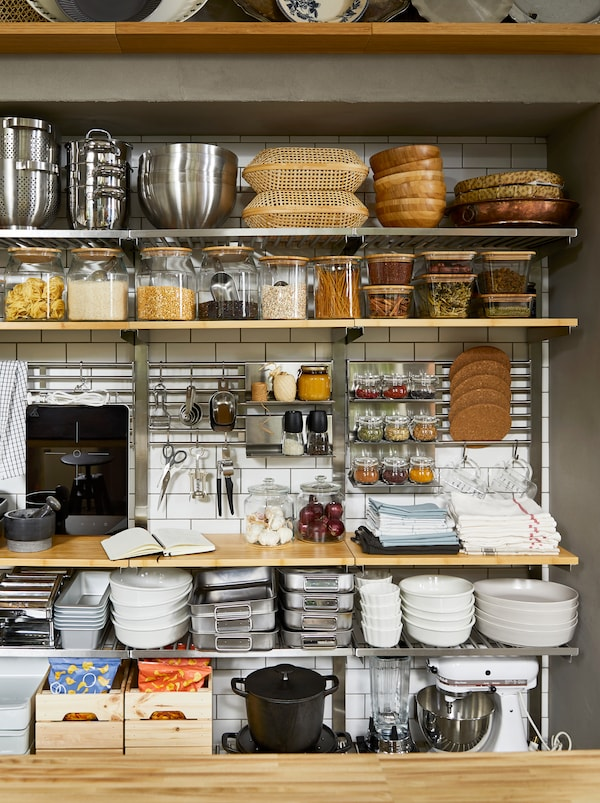 Pantry-style, open-storage kitchen wall with KUNGSFORS shelves, filled with dry goods in jars and cooking accessories.