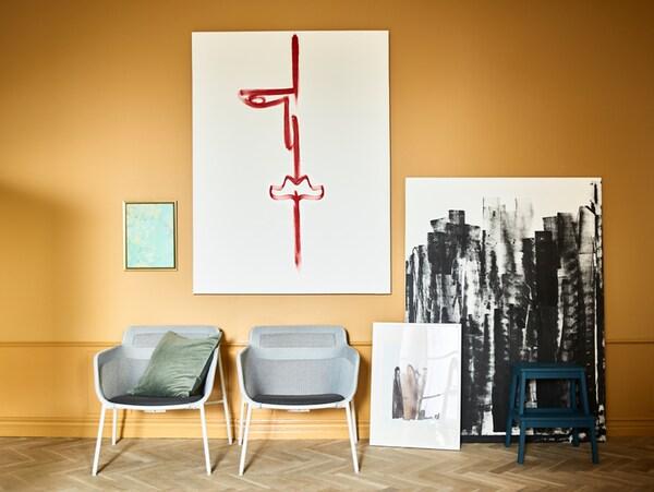 Pânze agățate și sprijinite pe un perete ocru, cu câteva tușe de pensulă negre și roșii pe ele și cu două scaune în fața lor.