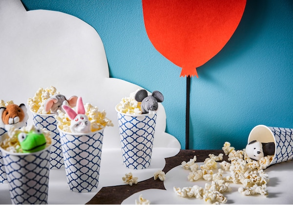 Paper cups are filled with popcorn and topped with a finger puppet. One cup is tipped over with popcorn spilling out.