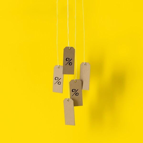 Papierové visačky s % na žltom pozadí symbolizujúce zľavy pre členov IKEA Family.