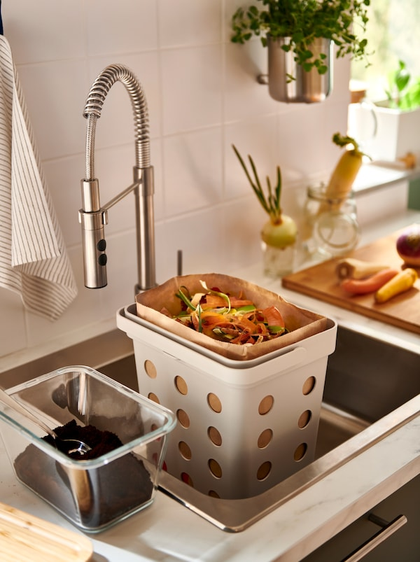 Papirna kesa puna ostataka hrane u HÅLLBAR korpi za organski otpad u sudoperi, tegle s iskorišćenim zrnima kafe pored.