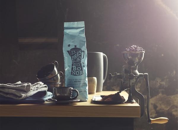 Paquet de café, mugs et moulin à café traditionnel rempli de grains de café.