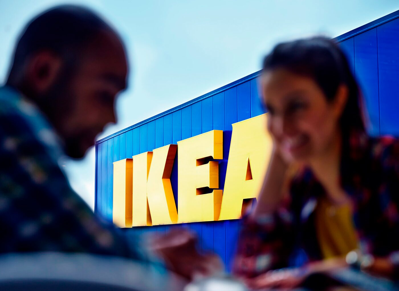 Par pred pročeljem trgovine IKEA, z izostrenim živo rumenim logotipom trgovine IKEA.