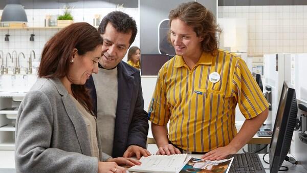 Pár si listuje brožurou, přičemž u nich stojí zaměstnanec IKEA a odpovídá na jejich otázky.