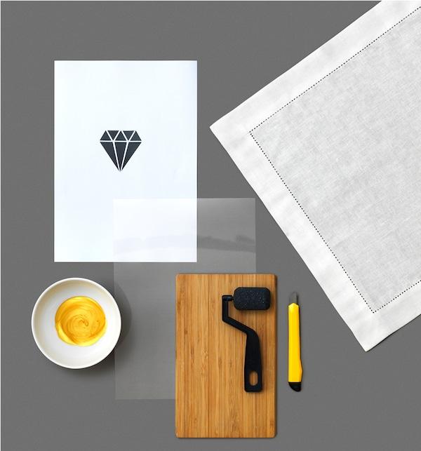 Para criar estampagens em forma de diamante nos guardanapos de linho GULLMAJ da IKEA, vai precisar de uma tábua de cortar de madeira, uma faca multiusos, tinta dourada numa tigela, uma folha de papel com um molde, um guardanapo branco, um rolo para tinta e uma folha de plástico.