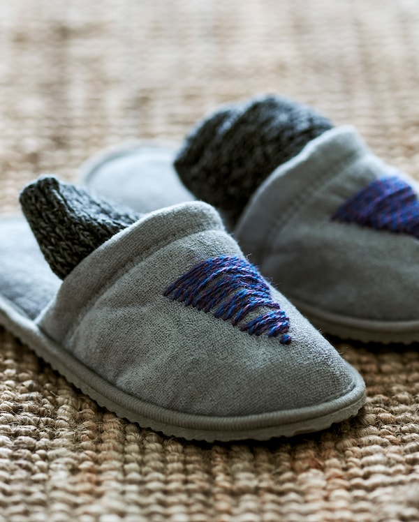 Пара серых тапочек на джутовом ковре, украшенных спереди простой вышивкой синими шерстяными нитками в виде елки.