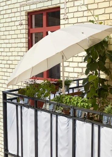 Parasol SAMSÖ/GRYTÖ blanco inclinado para tapar el sol y dar sombra a un balcón.