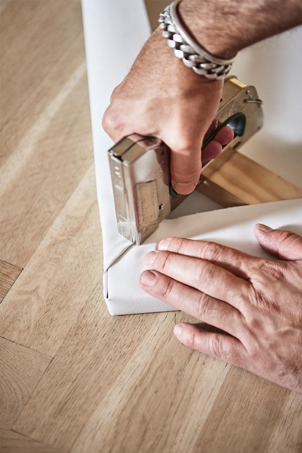 Parchet din lemn, cu mâinile unui bărbat capsând o bucată de pânză albă pe colțul unei rame foto din lemn.