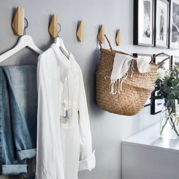 Pared con cinco ganchos de bambú IKEA SKUGGIS utilizados para colgar prendas y una cesta.