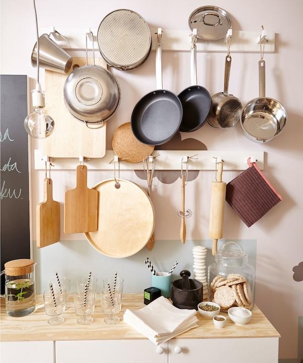 Pared de cocina con ollas, cacerolas y utensilios de cocina colgados de ganchos.