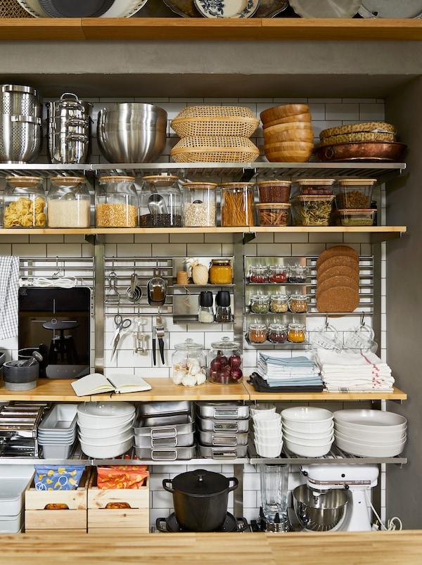 Pared de cocina tipo despensa, de almacenamiento abierto con estantes KUNGSFORS, llena de productos secos en frascos y accesorios de cocina.