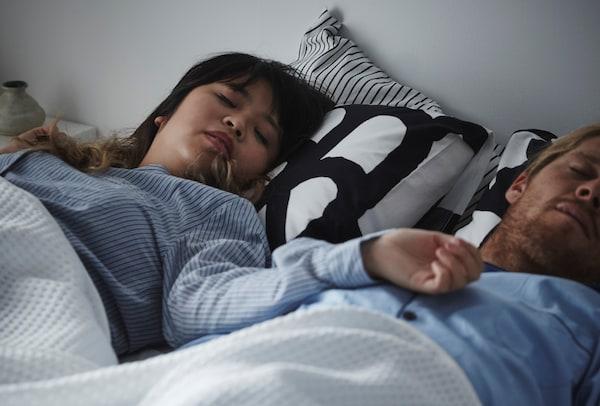 Pareja durmiendo en un dormitorio de matrimonio