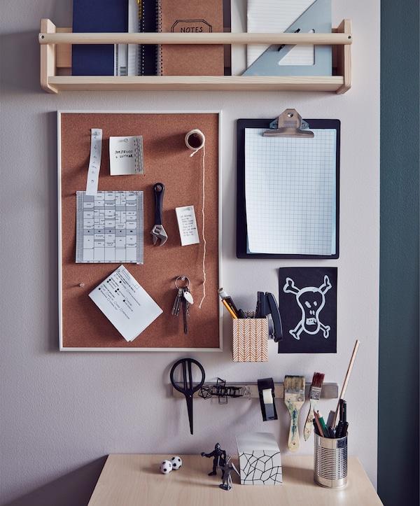 Paret al costat d'un escriptori amb prestatgeria, un portapapers i un tauler d'anuncis.