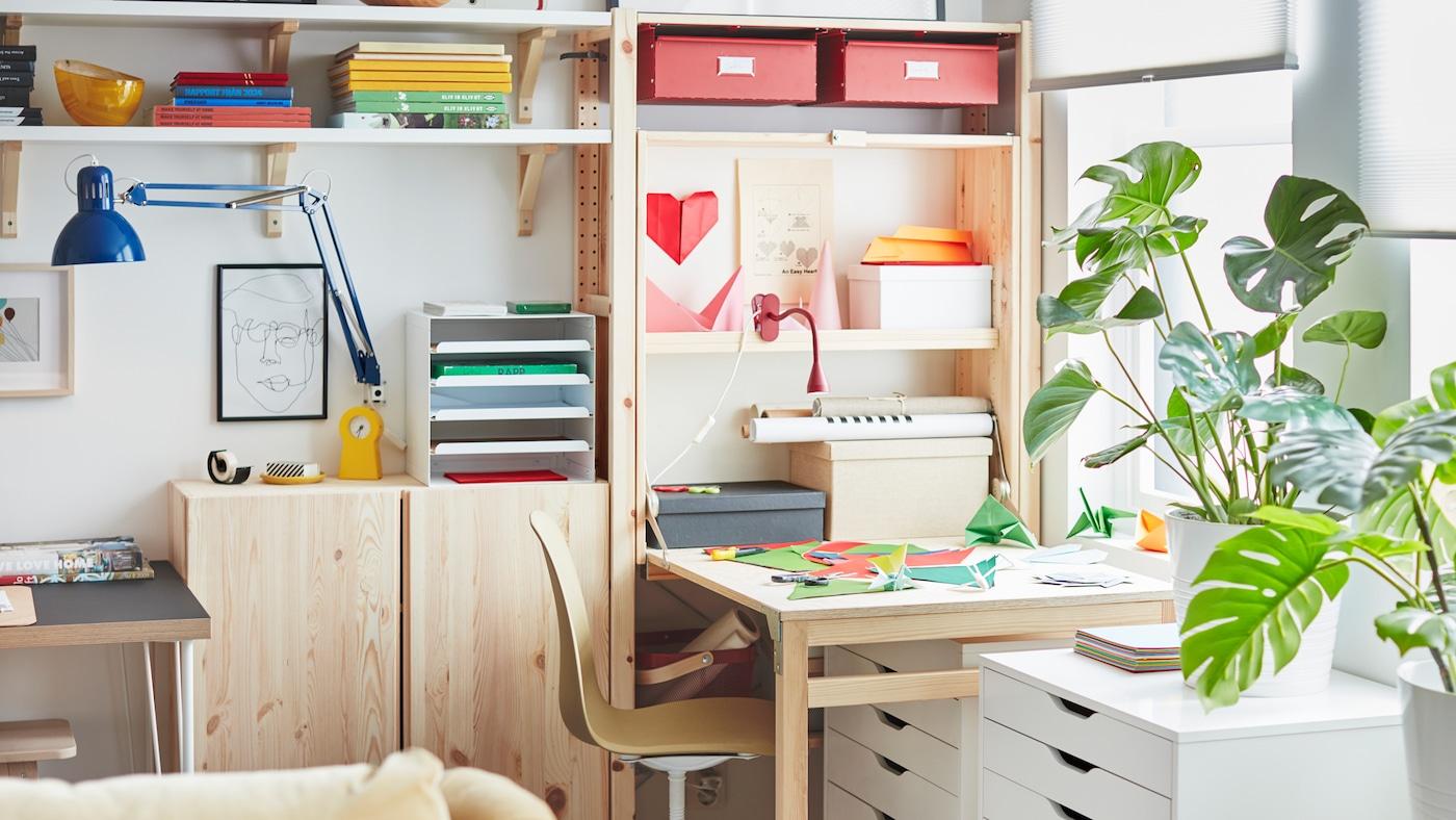 Parete con combinazione di scaffali IVAR e postazione di lavoro creata con un tavolo a ribalta, coperto da fogli colorati.