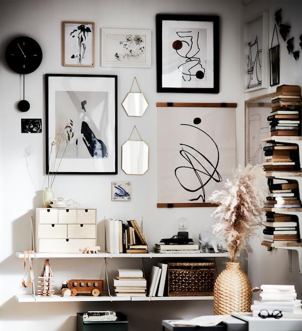 Parete con cornici, contenitori, libri, un orologio, giocattoli e un vaso, tutti nei toni del bianco, nero e beige.