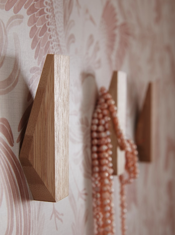 Parete di un ingresso con tre ganci SKUGGIS in legno di forma geometrica, su uno dei quali è appesa una collana.