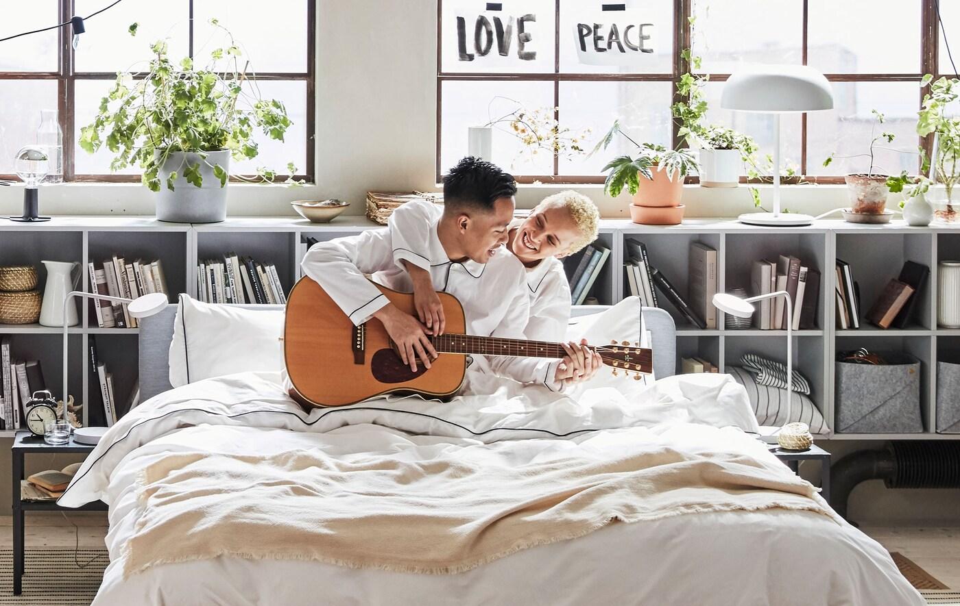 Pari soittaa sängyllä kitaraa teollisuustyylisessä loft-asunnossa.