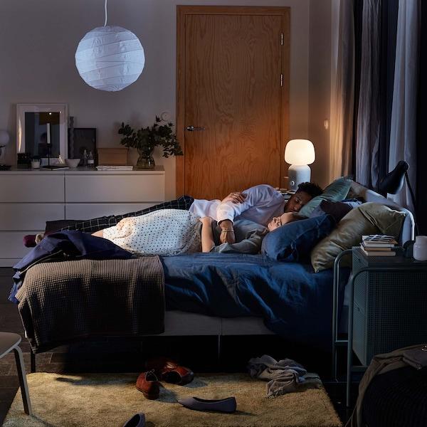Pariskunta nukkuu hämärässä huoneessa.