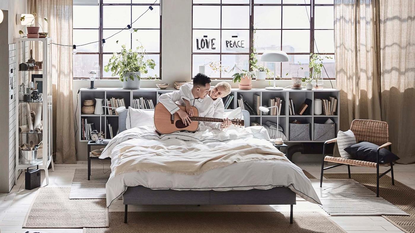 Pariskunta soittaa kitaraa SLATTUM-sängyllä