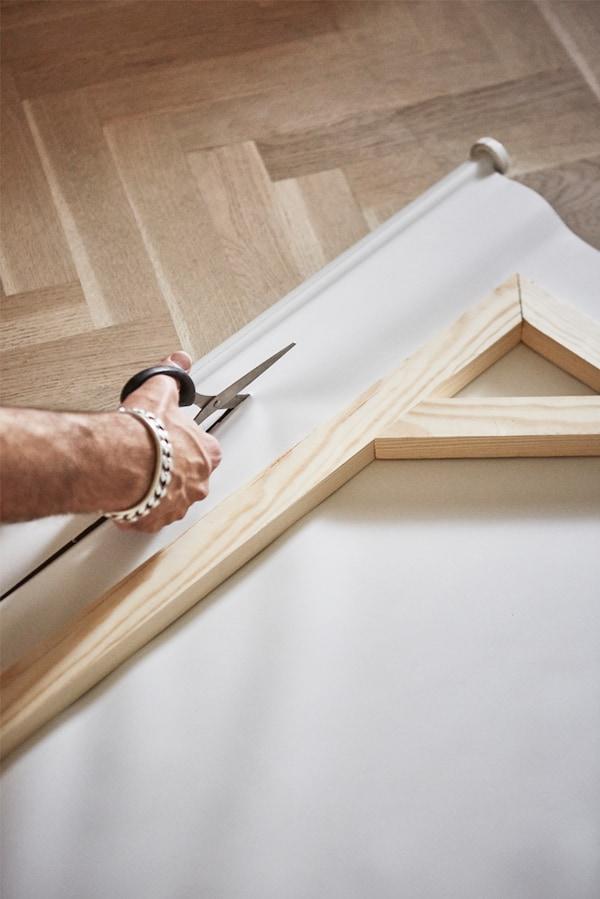 Parquet sur lequel un homme découpe la toile d'un store de fenêtre à l'aide de ciseaux, un cadre en bois posé au-dessus de la toile.