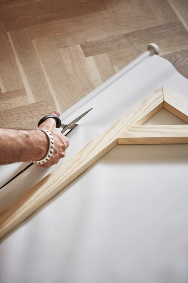 Parquet wooden floor with man cutting a canvas window blind with scissors and a wooden picture frame on top of the canvas.