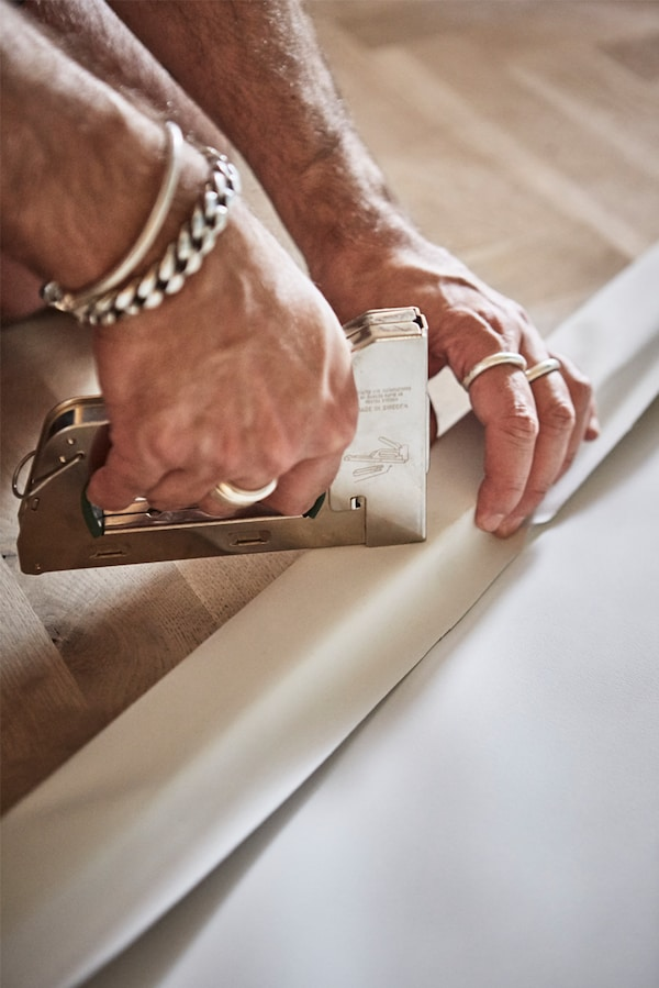 Parquet wooden floor with man's hands stapling a piece of white canvas to a wooden picture frame with a staple gun.