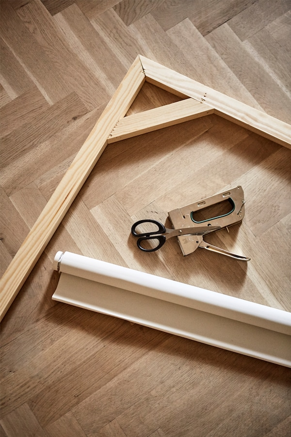 Parquet wooden floor with wooden picture frame, rolled up canvas window blind, staple gun and pair of scissors.