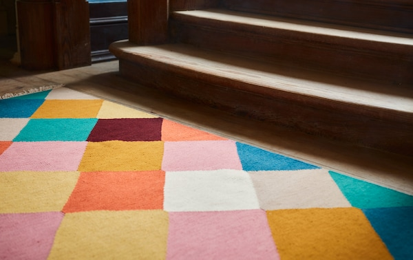 Part of a sunlit VINDERÖD wool rug with a multicolored, checkered pattern that lies at the base of a staircase.