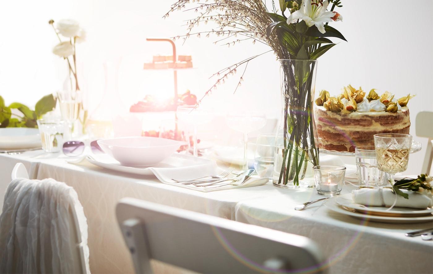Parte de uma mesa comprida, arranjada num estilo romântico e requintado, com móveis, toalha, loiça, bolo, prato de bolos e flores em branco.