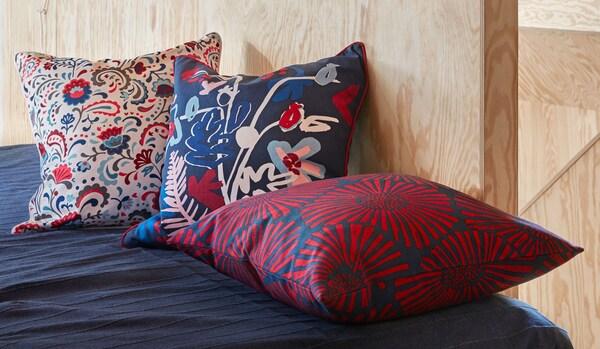 Parte de una cama hecha junto a una pared de paneles de madera. Tres cojines con laboriosos estampados decoran la cama.