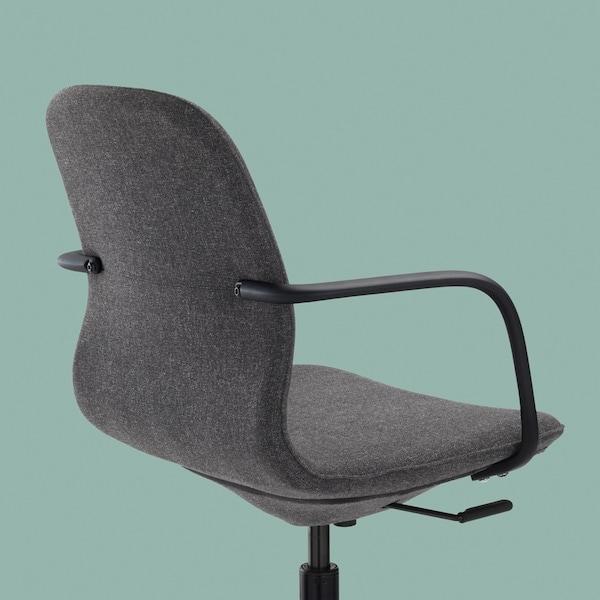 Parte traseira, lateral e assento de uma cadeira giratória LÅNGFJÄLL com apoios de braços em cinzento escuro e preto sobre um fundo em azul petróleo claro.
