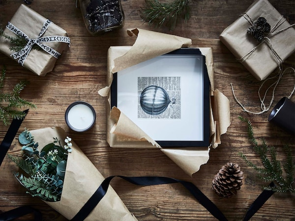 Partially wrapped gifts including a picture frame, a flower bouquet and a candle on a rustic wooden floor