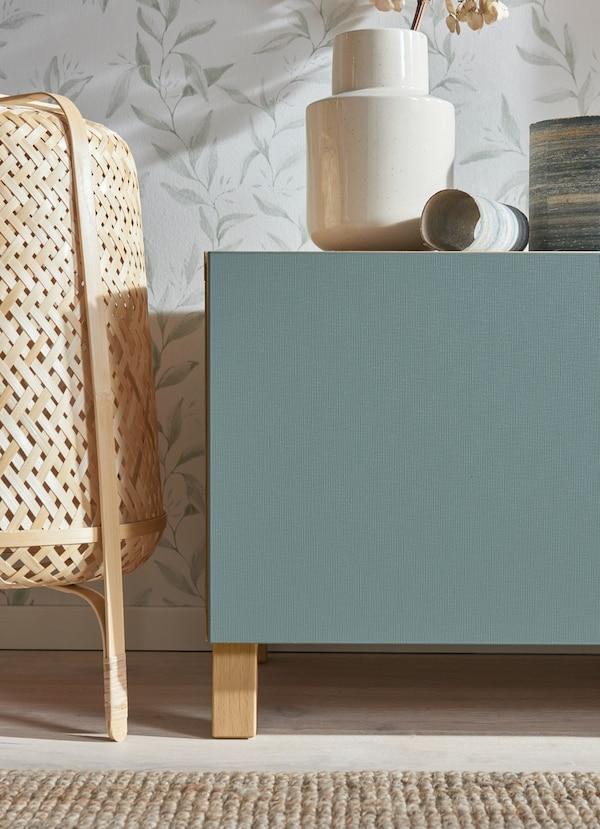 Particolare di un mobile basso in legno chiaro con antina turchese.