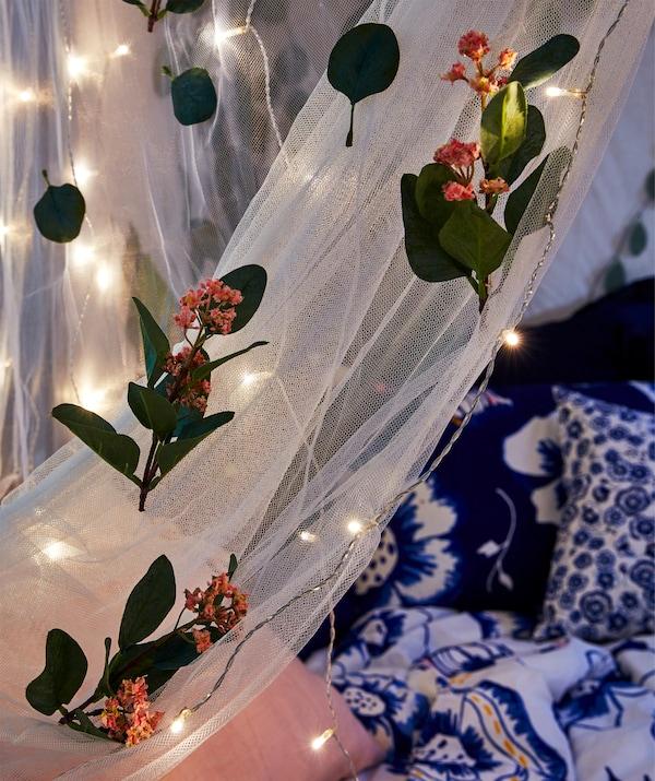 Partie de moustiquaire drapée sur un lit la nuit, décorée de fleurs artificielles et de guirlandes lumineuses.