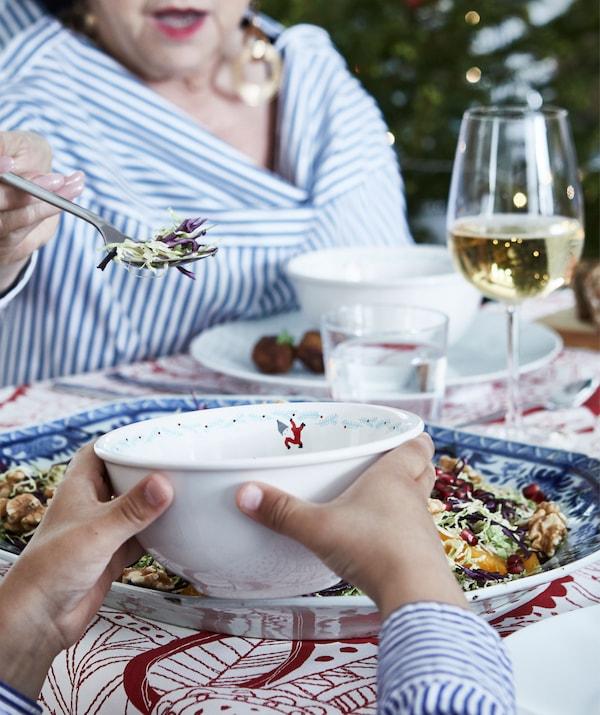 Partie d'une table de fête, avec assiettes et verres remplis. Une personne âgée dépose de la nourriture dans un bol tenu par un enfant.